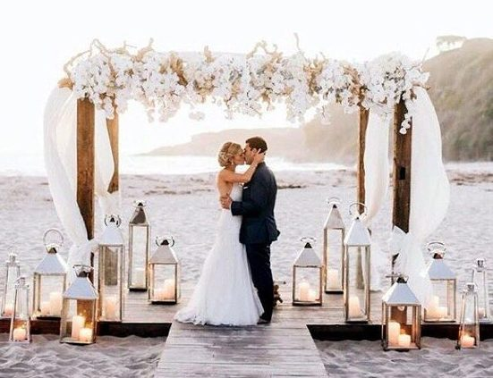 bride and groom kissing under arch on beach